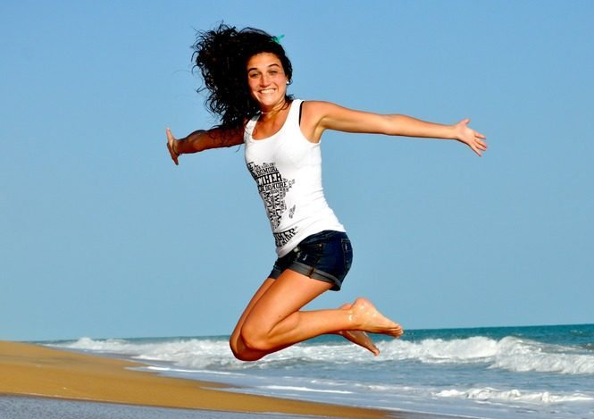 A woman jumps, very excited about the many health and mood benefits of movment