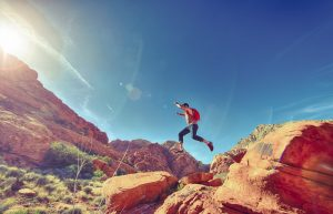 man jumping happily over rocks